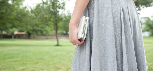 Donna in vestito d'argento brillante che tiene il portafoglio all'aperto.