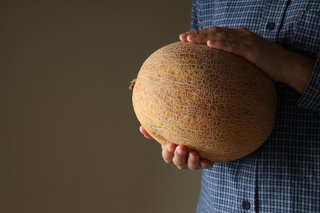 La donna in camicia tiene il cesto con il melone