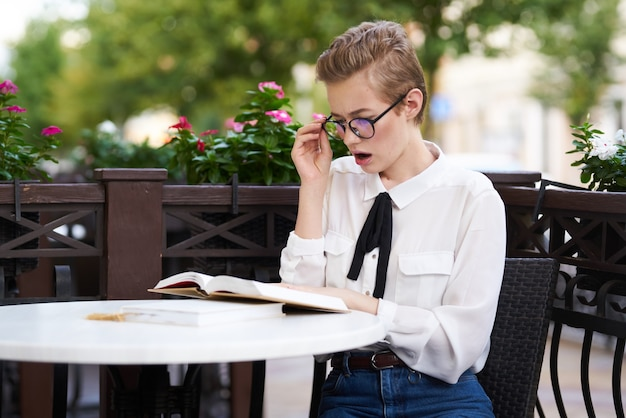 Donna in camicia cravatta al tavolo in bicchieri caffè sul libro aperto scienza educazione viso