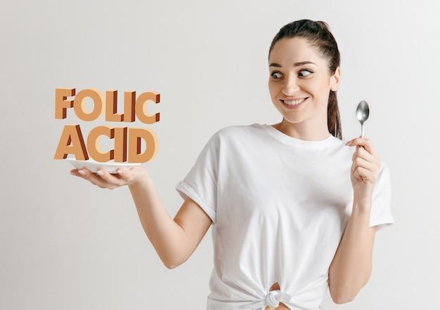 Donna in camicia con la gente isolata su bianco. modello femminile in possesso di un piatto con lettere della parola acido folico.