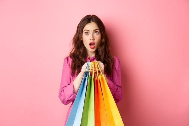 Donna scioccata dagli sconti, alzando lo sguardo con la faccia stupita, tenendo le borse della spesa, in piedi contro il muro rosa.