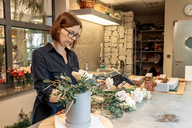 La lavoratrice del negozio, l'organizzatrice di matrimoni lavora con i fiori per creare bouquet di fiori.