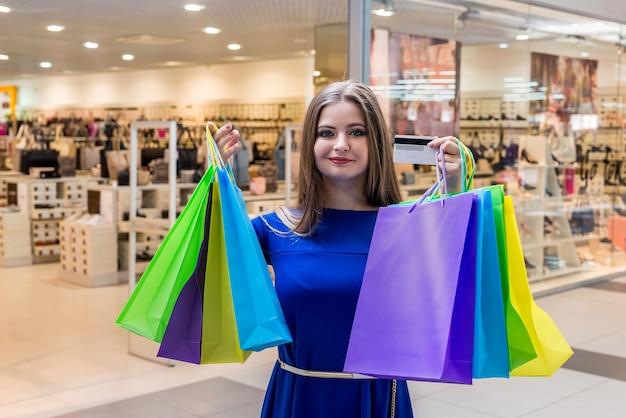 Cliente della donna che mostra le sue borse variopinte in centro commerciale