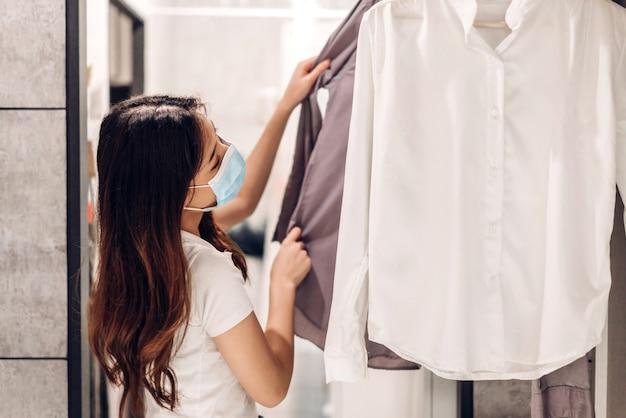 Donna shopping e scelta di vestiti in negozio