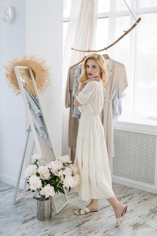 Acquisto della donna che sceglie i vestiti che guardano nello specchio