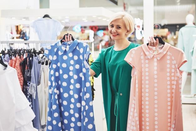 Abbigliamento donna shopping. shopper guardando abbigliamento al chiuso in negozio. bello modello femminile caucasico asiatico sorridente felice