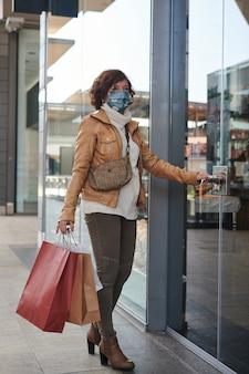 Donna che fa shopping in un centro commerciale con maschera facciale, new normal, covid-19
