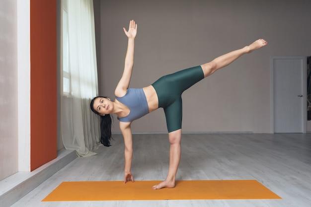 Una donna in leggings corti e una maglietta un praticante di yoga esegue l'esercizio ardha chandrasana la posa della mezzaluna in studio vicino alla finestra