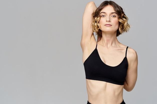 La donna in maglietta corta va a fare sport su un esercizio di sfondo grigio
