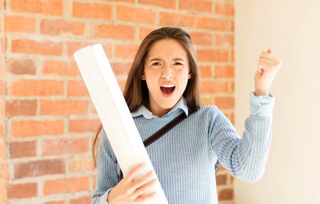 Donna che grida in modo aggressivo con un'espressione arrabbiata o con i pugni chiusi per celebrare il successo