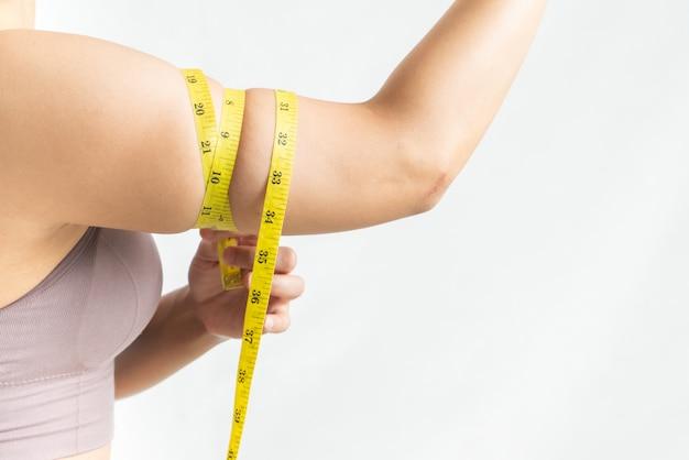 Lo spettacolo e la compressione della donna stringono, il grasso corporeo del braccio con nastro adesivo di misura