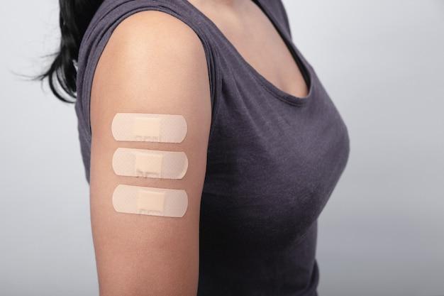 Donna che mostra il braccio con cerotti dopo il vaccino covid-19, il virus della mutazione, l'immunizzazione del coronavirus