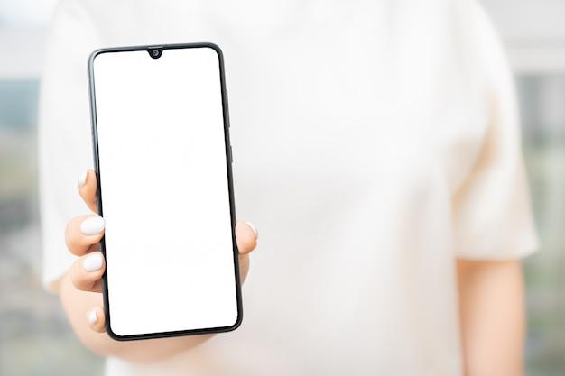 Donna che mostra telefono cellulare con lo schermo in bianco. modello