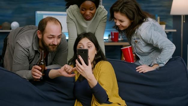 Donna che mostra video comici al telefono ai suoi amici multirazziali che socializzano insieme durante la festa notturna. gruppo di persone di razza mista sedute sul divano, bevendo birra, rilassandosi in soggiorno