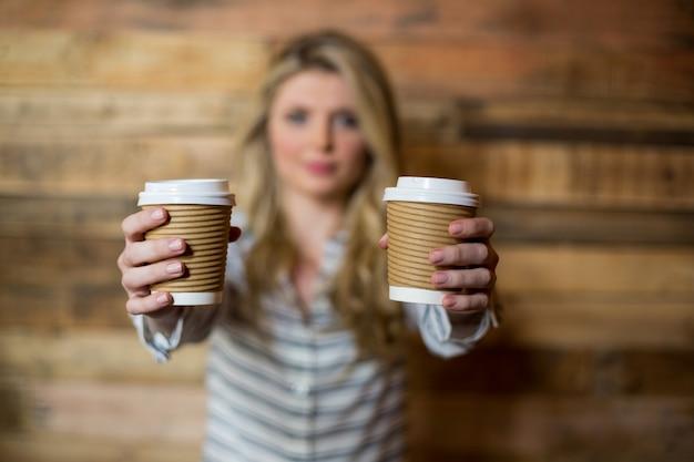 Donna che mostra la tazza di caffè eliminabile