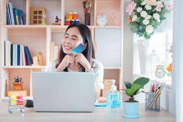Donna che mostra felicità dopo lo shopping online con lo stile di vita new normal per l'auto quarantena durante lo scoppio della malattia da corona virus (covid-19)