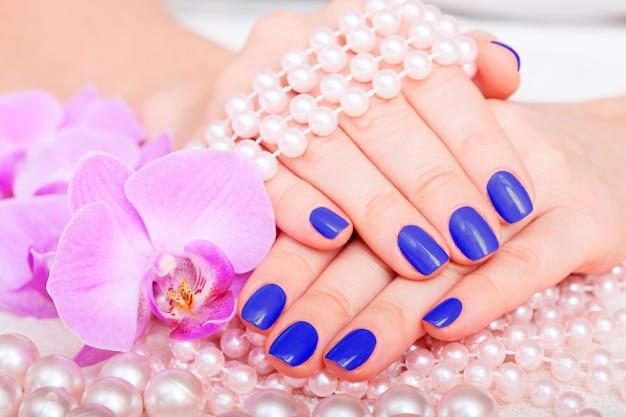 Donna che mostra le sue belle unghie con manicure e fiori