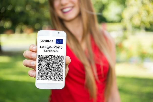 Donna che mostra il suo certificato europeo di vaccino contro il covid, chiamato anche green pass