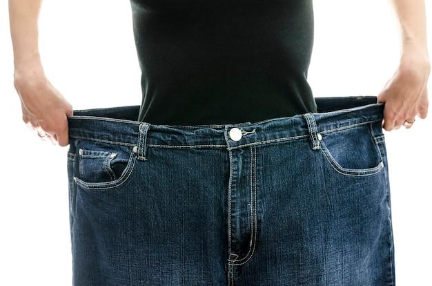 Donna che mostra quanto peso ha perso indossando i suoi vecchi jeans. concetto di perdita di peso.