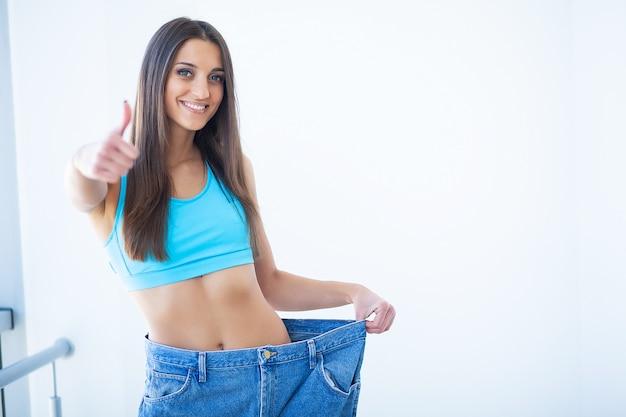 Donna che mostra quanto peso ha perso