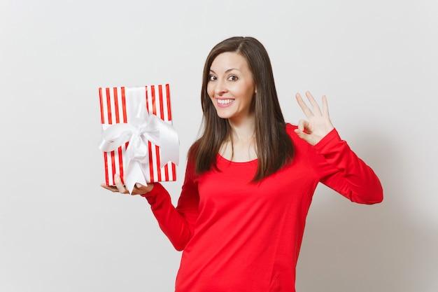 Donna che mostra gesto ok, con scatola regalo rossa con regalo, nastro isolato su sfondo bianco. per la pubblicità. san valentino, giornata internazionale della donna, natale, compleanno, concetto di vacanza