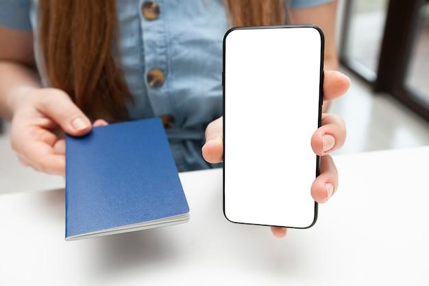 La donna che mostra il telefono con lo schermo in bianco e dà il passoprt. progettazione di mockup