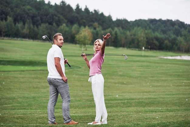 Donna che mostra qualcosa dietro. coppia di giocatori di golf con bastoni in mano in piedi sul prato.