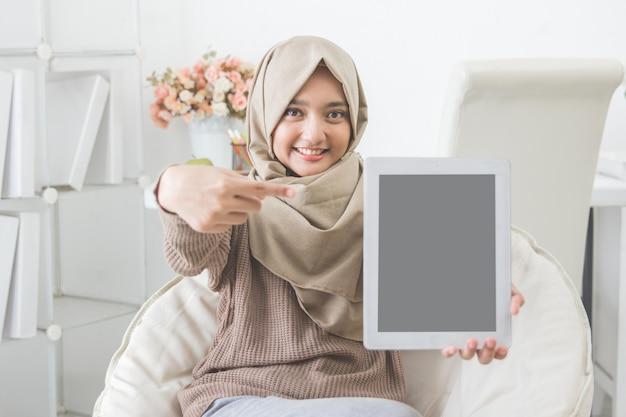 Donna che mostra lo schermo e il sorriso della compressa