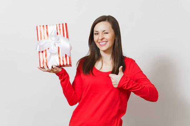 Donna che mostra pollice in su, tenendo la scatola presente a strisce rosse con nastro isolato su sfondo bianco. per la pubblicità. san valentino, giornata internazionale della donna, natale, compleanno, concetto di vacanza