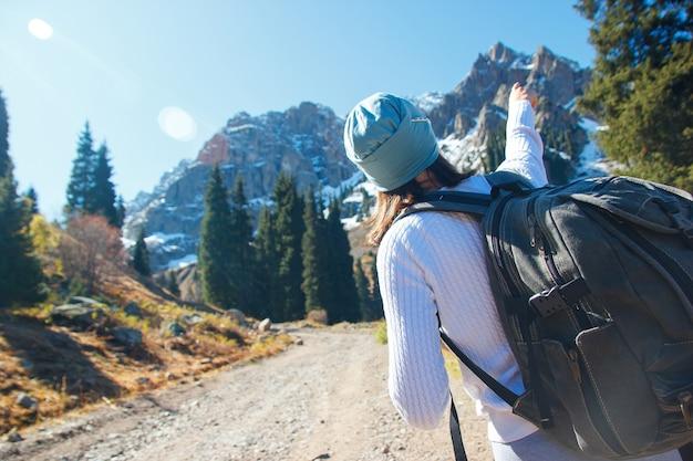 La donna mostra la sua mano in cima alla montagna. cima della montagna di neve.