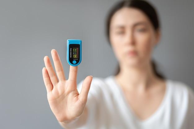 Una donna mostra la sua mano con un pulsossimetro sul dito indice. ritratto sfocato. sfondo blu. il concetto di misurazione dell'ossigeno nel sangue.