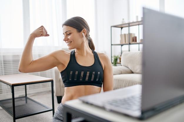 La donna mostra i suoi muscoli, allenamento fitness online al computer portatile. persona di sesso femminile in abbigliamento sportivo, allenamento sportivo internet, interno della stanza