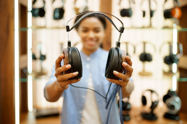 La donna mostra le cuffie vintage nel negozio di componenti audio. persona di sesso femminile nel negozio di musica, vetrina con auricolari, acquirente nel negozio multimediale