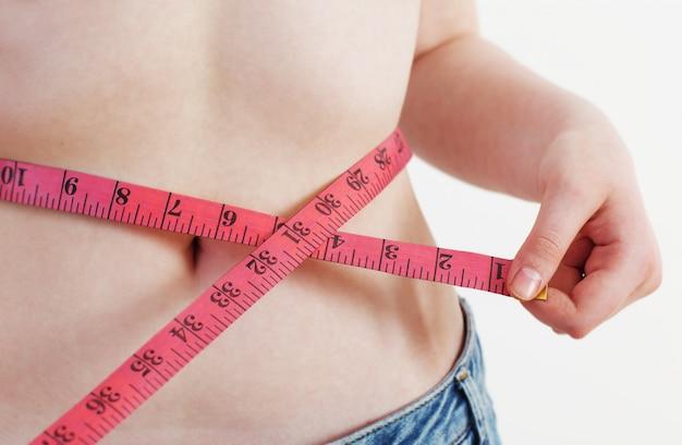 La donna mostra la perdita di peso sulla parete di bianco del fondo