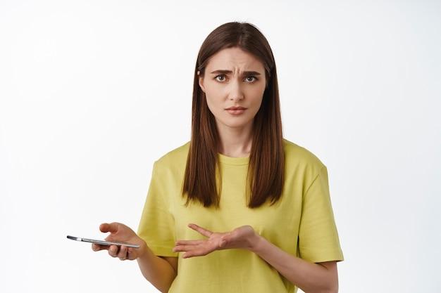 Donna che scrolla le spalle, tiene in mano lo smartphone e sembra perplessa su smth online, problema sul telefono cellulare, in piedi su bianco