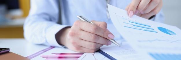 Documento di firma della donna con i grafici con il primo piano della penna a sfera.