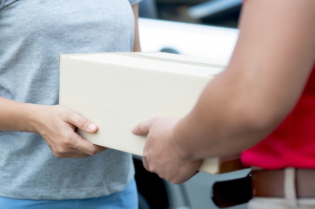 Donna che firma per pacchi da consegna porta a porta e ordinazione online