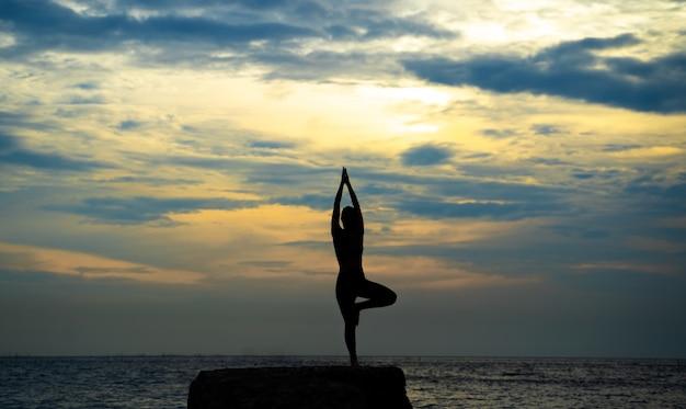 Yoga di pratica della siluetta della donna alla spiaggia