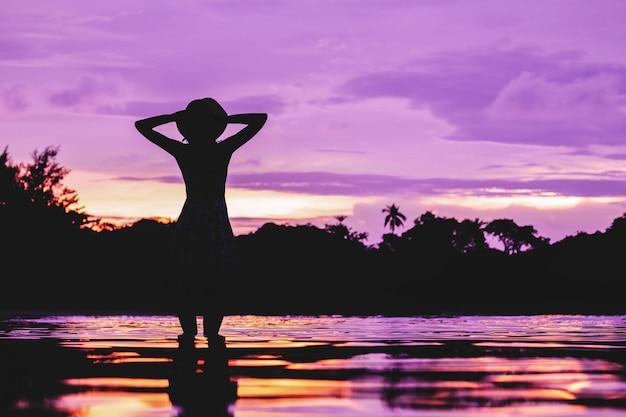 Siluetta della donna sopra il cielo di tramonto con la riflessione in acqua Foto Premium