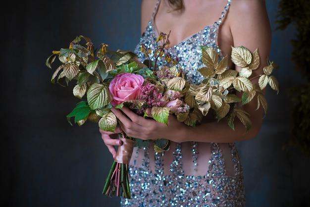 La donna in abito d'argento tiene un bellissimo mazzo decorato di fiori e verde su sfondo grigio, riprese in primo piano