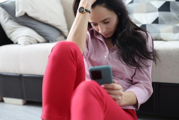 La donna si siede sul pavimento vicino al divano e dorme