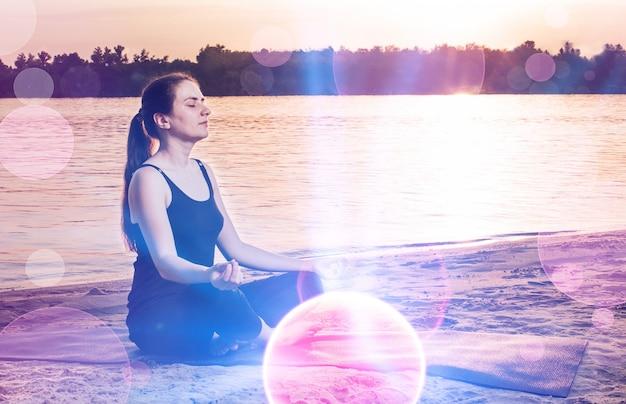 Una donna si siede sulla spiaggia nella posizione del loto e si concentra, medita e desidera