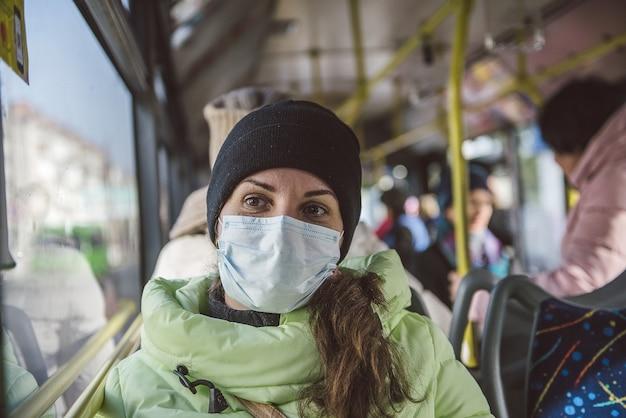 Donna si siede in un autobus urbano in una maschera protettiva medica. protezione contro il coronavirus covid-19 nei trasporti pubblici.