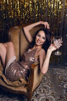 La donna si siede su una sedia club e tiene in mano un bicchiere di vino