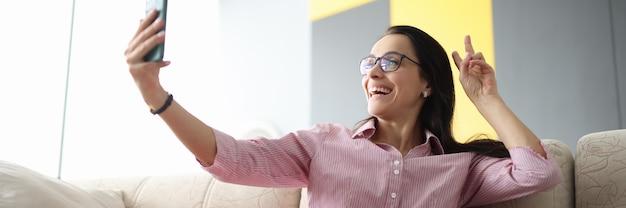 La donna si siede sul divano e, con un sorriso, saluta il suo interlocutore durante la trasmissione video