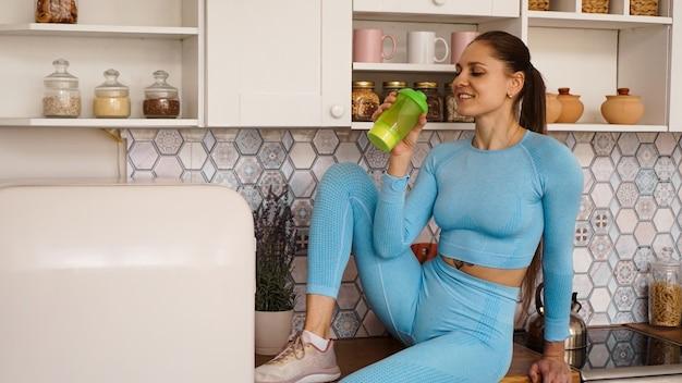 Una donna siede sul piano di lavoro in cucina con una bottiglia verde per l'alimentazione sportiva o l'acqua. concetto di stile di vita sano.