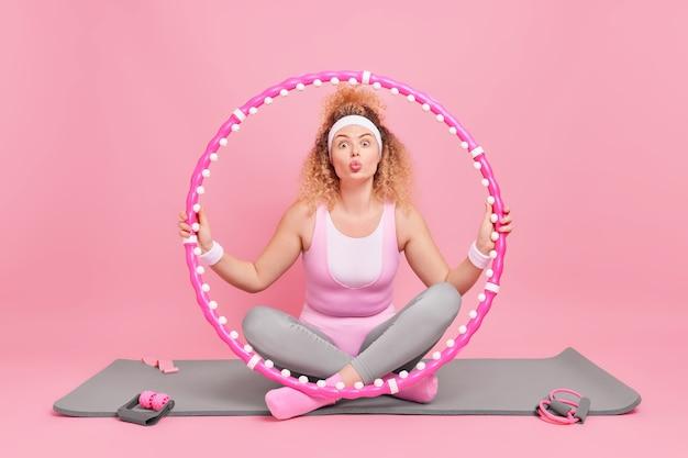 La donna si siede a gambe incrociate sul tappetino fitness tiene l'hula hoop mantiene le labbra arrotondate vuole baciarti pose