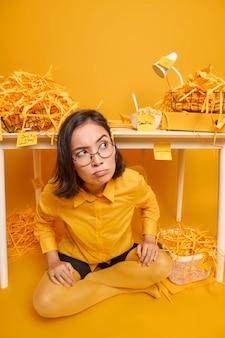 La donna si siede a gambe incrociate sul pavimento guarda da parte posa vicino al posto di lavoro sviluppa un nuovo progetto di design su giallo