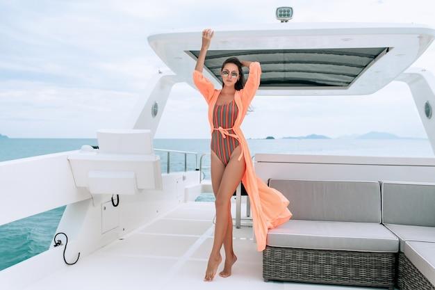 La donna si siede sul ponte di uno yacht