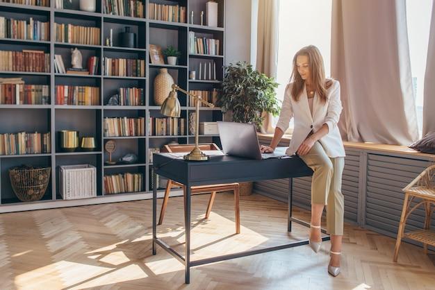 La donna si siede sul bordo della scrivania e usa un laptop.